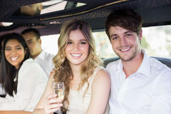 Well dressed people drinking champagne in a limousine Royalty Free Stock Photo