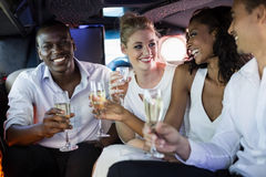 Well dressed people drinking champagne in a limousine Stock Photos