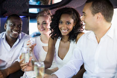 Well dressed people drinking champagne in a limousine Royalty Free Stock Photos