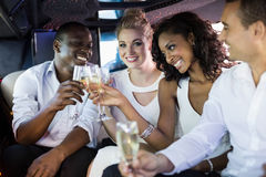 Well dressed people drinking champagne in a limousine Stock Image