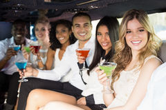 Well dressed people drinking cocktails in a limousine Stock Images
