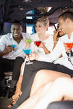 Well dressed people drinking cocktails in a limousine Royalty Free Stock Image