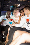 Well dressed people drinking cocktails in a limousine Stock Image