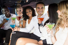 Well dressed people drinking cocktails in a limousine Royalty Free Stock Photo