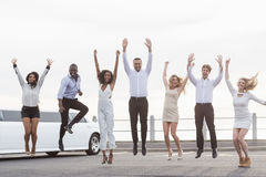 Well dressed people jumping next to a limousine Stock Images