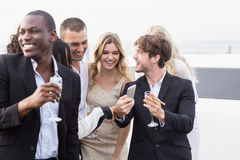 Well dressed people looking smartphone next to a limousine Royalty Free Stock Photography
