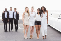 Well dressed people posing next to a limousine Royalty Free Stock Photography