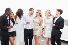 Well dressed people posing next to a limousine Royalty Free Stock Photos