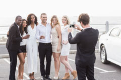 Well dressed people taking pictures next to a limousine Royalty Free Stock Image