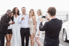 Well dressed people taking pictures next to a limousine Stock Images
