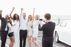 Well dressed people taking pictures next to a limousine Stock Image