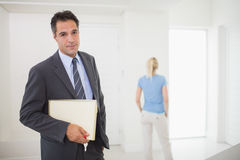 Well dressed real estate agent with blurred woman in background Stock Images