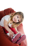Well-dressed small girl sit on a chair Royalty Free Stock Photos
