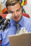 Well dressed smiling radio host moderating holding clipboard. In studio at college Stock Photo