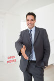 Well dressed smiling real estate agent offering handshake Stock Image