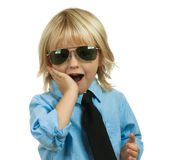 Well-dressed, surprised cute boy on white. Portrait of a well-dressed surprised young school boy with his hand on his cheek wearing sunglasses. Isolated on white stock image