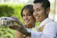 Well-dressed teenage couple taking photograph outside Royalty Free Stock Images