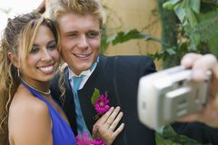 Well-dressed teenager couple taking picture outside school dance Stock Image