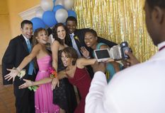 Well-dressed teenagers posing for video camera at school dance Royalty Free Stock Image
