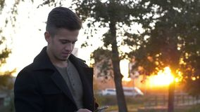 Well-dressed trendy man talking with mobile phone in a city on sunset time. Young dressed trendy man talking with mobile phone in a city on sunset time stock video