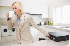 Well dressed woman drinking coffee while holding briefcase in kitchen Stock Images