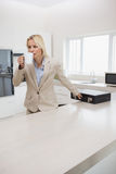 Well dressed woman drinking coffee while holding briefcase in kitchen Royalty Free Stock Photos