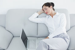 Well dressed woman resting while using laptop at home Royalty Free Stock Photos