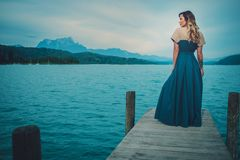 Well-dressed woman sitting on the wooden pier with mountain river view. Stock Photos