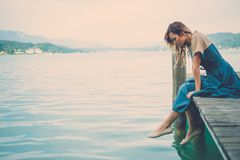 Well-dressed woman sitting on the wooden pier with mountain river view. Stock Photography
