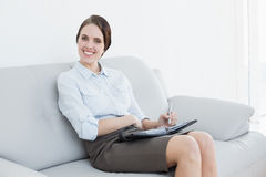 Well dressed woman using personal organizer at home Royalty Free Stock Photography