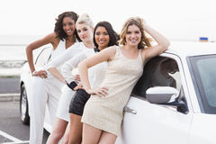 Well dressed women posing leaning on a limousine Stock Image