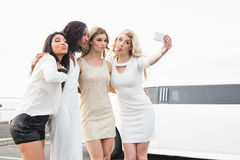 Well dressed women taking a selfie next to a limousine Royalty Free Stock Photos