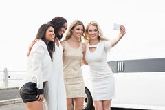 Well dressed women taking a selfie next to a limousine Royalty Free Stock Photography