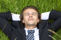 Well-dressed young businessman is resting. In a field Royalty Free Stock Images