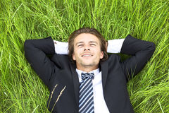 Well-dressed young businessman is resting. In a field Royalty Free Stock Photography