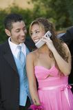 Well-dressed young couple using cell phone outside Stock Photo