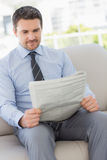 Well dressed young man reading newspaper at home Stock Images