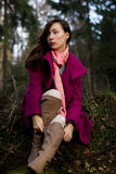 Well-dressed young woman in pink topcoat sitting in forest Royalty Free Stock Image