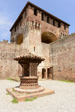 Well and dungeon, Soncino Castle. View of the well and of one of the massive dungeon in the main inner court in the ancient Sforzesco Castle, shot in bright royalty free stock photo