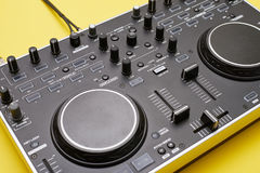 Well-equipped DJ panel on yellow background, flat lay. Close-up of well-equipped DJ panel on yellow background Stock Photography