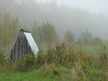 A well in the field during the fog. Nearby russian village royalty free stock image