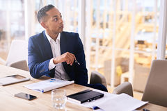 Well groomed businessman sitting at conference table in tailored suit Royalty Free Stock Images