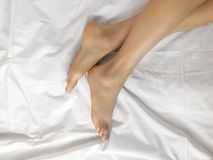 Well-groomed female bare feet on a white sheet, top view, closeup royalty free stock photo