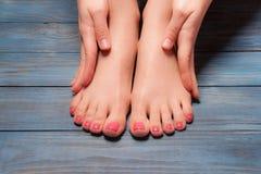 Well-groomed female feet on wooden floor Stock Images