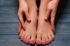 Well-groomed female feet on wooden floor Stock Photography
