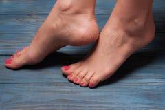 Well-groomed female feet on wooden floor Royalty Free Stock Image