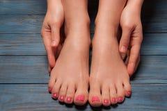 Well-groomed female feet on wooden floor Royalty Free Stock Photos