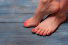 Well-groomed female feet on wooden floor Royalty Free Stock Images