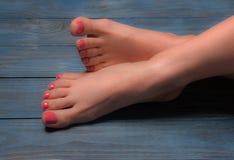 Well-groomed female feet on wooden floor Stock Photo