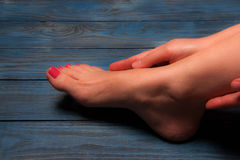 Well-groomed female feet on wooden floor Royalty Free Stock Photography